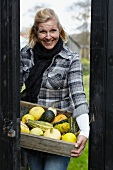 Woman holding wooden crate of ornamental gourds