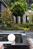 Courtyard garden with floating, spherical lamps in black pool and ornamental screen in background