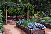 Raised beds with wooden surrounds in lush garden with simple table and benches on wooden decking in background