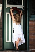 Little girl hanging a wreath on a door