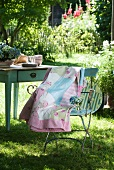 Patchwork blanket with delicate patterns draped over garden chair in front of old wooden table in summer garden