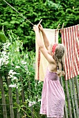 Pretty tea towels hanging on washing line as screen along garden fence