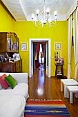 Weisses Polstersofa neben antikem Buffet und offene Flügeltür in einem gelb getönten Wohnraum