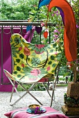 Pennants and colourful butterfly chair on summery balcony