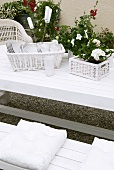 Crockery and potted flowering plants in wicker baskets on white garden table with matching bench