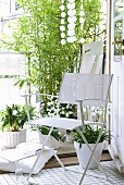 White folding chair in front of potted flowering plants and bamboo on balcony