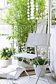 Weisser Klappstuhl vor Topfblumen und Bambusstrauch auf Balkon