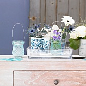 Blue and white flowers in vases on cabinet