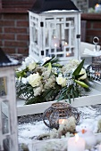 Winter wreath with roses and lilies, lanterns and tea light holders