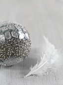 Silver Christmas tree bauble and white feather
