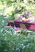 Voyeuristischer Blick durch das verschwommene Gartengrün auf verschiedene Stühle um einen sommerlich gedeckten Tisch mit Bougainvillea-Topf