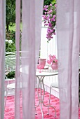 View through panels of lilac curtain to feminine, shabby chic seating area on terrace with delicate bistro furniture and decor in shades of pale rose and deep pink