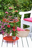 White wooden deck with pink decorations and potted plants on small, red serving table with bottle rack