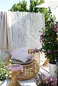 Rattan-Lounger, Hocker und Bambusmatte als Sichtschutz auf einer Terrasse
