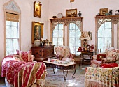 Living room with a style mix - classic, floral upholstered furniture and antique chest of drawers under baroque paintings