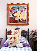 Modern Pop Art painting above a rustic country bed with floral pillows and a plaid bedspread
