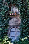 Efeuberankte Fassade eines traditionellen Landhauses mit dekorativ geschnitzen Fenstern