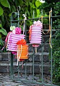 Concertina lanterns hanging on garden gate and decorated with ribbons, paper flowers and strips of paper