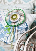 Hand-crafted cardboard rosette with decorative ribbons on cushion