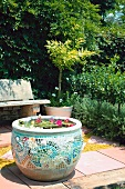 Water lily pool in a mosaic clay pot on a paved seating area in the garden