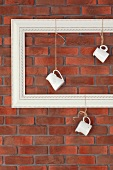 Milk jugs hanging from empty picture frame against brick wall