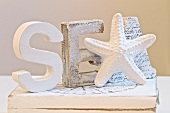 White-painted wooden letters and starfish figurine on wooden box