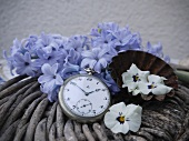 Vintage pocket watch and petals on rattan basket