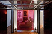 Glass and steel ceiling above foyer in open-plan hallway with transparent coloured glass partition separating lounge