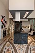 Hypermodern kitchen island with extractor hood in open-plan interior with ornamental terrazzo floor