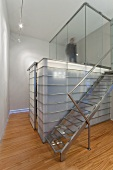 Stainless steel staircase next to glass and steel installation below landing with glass walls