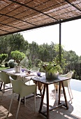 Dining area on roofed terrace with bamboo mat pergola