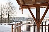 Ausschnitt einer Holzstütze mit rustikalem Dachanschluss und Holzzaun in verschneiter Berglandschaft