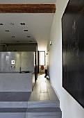 Open-plan designer bathroom - bathtub on platform and view into hallway with window