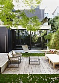 Seating area on terrace with wooden decking in front of modern city house