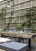 Tisch mit rustikalen Holzbohlen vor Holzwand mit Kletterpflanzen im Innenhof