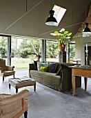 Sitzgarnitur im Raucherzimmer mit schlammgrüner Wandfarbe, Betonboden und Glasfront zum Garten