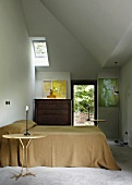 Double bed, two gilt Meret Oppenheim Traccia tables and chest of drawers in bedroom