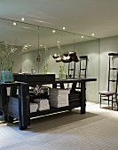 Black-painted workbench as washstand in bathroom with mirrored wall and Chiavari chair in background