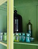 Verschiedene Färbemittel in Apothekerflaschen in einem grün angemalten Schrank