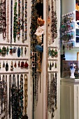 Necklaces and earrings hanging on wall hooks