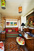 Sleeping and work areas in simple bedroom - bamboo four poster bed with colourful striped cover and upholstered stool in foreground at antique bureau