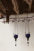 Blue glass tealight holders and lantern hanging from wooden ceiling beams