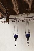 Hängende Windlichter aus blauem Glas und eine Laterne an Holzbalken befestigt