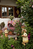 Ceramic figurines in garden and on veranda of farmhouse
