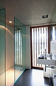 Purist bathroom with striped frosted French windows and recessed spotlights in concrete ceiling