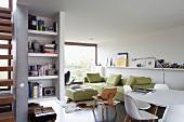 Lichtdurchfluteter Wohn/Essraum mit lindgrüner Sofagarnitur und weißem Eames Esstisch-Ensemble