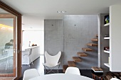 View from dining area of butterfly chair and cantilever wooden steps on exposed concrete wall; white kitchen counter in background