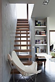 White butterfly chair in front of cantilever wooden steps of narrow interior staircase