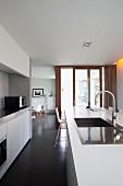 Blick über die weisse Küchentheke mit Einbauspüle auf Schiebefenstertüren zur Terrasse und Eames-Chairs am Esstisch im Hintergrund