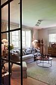 Traditioneller Wohnraum mit Antiquitäten und grauer Polstergarnitur in renoviertem Landhaus